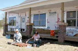 Neighbors lay bricks on a pathway leading up to a partially-constructed home in Shadowlake Village during the community's early days.