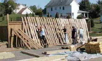 A team builds a fence between the neighboring Westover community and the still-under-construction Shadowlake Village, per town of Blacksburg requirements.